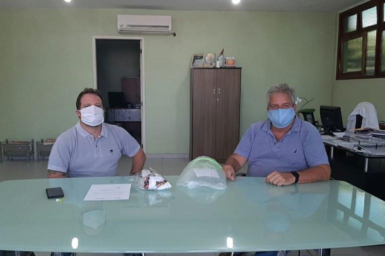 O diretor Victor Saraiva entrega os protetores faciais ao representante do município de Armação dos Búzios, Carlos Roballo