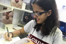 Jéssica Sanz, do 8º período do Curso de Licenciatura em Letras,  autografa exemplar de seu 3º  livro (Foto: Divulgação)