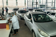 A equipe médica aplica a vacina na pessoa dentro do carro.Fotos: Divulgação