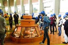 Estudantes observam o funcionamento de uma das turbinas de geração de energia.