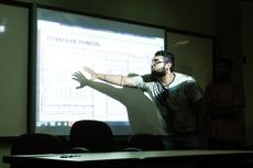 Integrante de equipe explica detalhe de projeto.