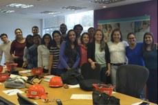 Alunos do SAEG com a professora Alline Morais (de blusa azul) e a gerente de Qualidade Ana Paula Sá (da direita para a esquerda, a terceira, de blusa branca)