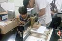 Os alunos Thiago e Mateus trabalham em uma estrutura de impressora 3D