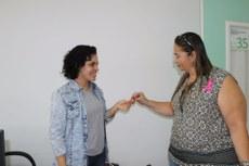 Paula Bastos entrega laço de fita da Campanha Outubro Rosa à servidora da Reitoria