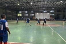 Equipes em quadra na disputa de futsal.